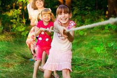 Group of happy children playing tug of war outside on grass. Kids pulling rope at park. Summer camp stock image