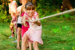 Group of happy children playing tug of war outside on grass. Kids pulling rope at park. Summer camp royalty free stock image