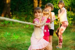 Group of happy children playing tug of war outside on grass. Kids pulling rope at park. Summer camp royalty free stock photo