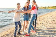 Group of children pulling rope during tug of war game on beach. Summer camp. Group of happy children pulling rope during tug of war game on beach. Summer camp Royalty Free Stock Photos