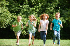 Group Of Happy Children Running Towards Camera Through Field Stock Photos