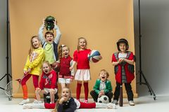 Group of happy children show different sport. Studio fashion concept. Emotions concept. Boys and girls like sport. Football, american football, baseball Royalty Free Stock Photo