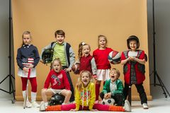 Group of happy children show different sport. Studio fashion concept. Emotions concept. Boys and girls like sport. Football, american football, baseball Royalty Free Stock Image