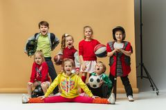 Group of happy children show different sport. Studio fashion concept. Emotions concept. Boys and girls like sport. Football, american football, baseball Stock Photos