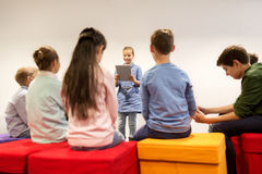 Group of happy children with tablet pc at school stock image