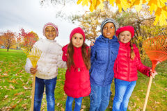Group of happy cute kids with rakes stand in park royalty free stock photography