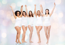 Group of happy different women celebrating victory. Happiness, friendship, beauty, body positive and people concept - group of happy different women in white Stock Photo