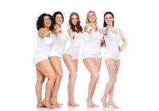 Group of happy different women pointing on you. Choice, friendship, beauty, body positive and people concept - group of happy different women in white underwear Royalty Free Stock Images