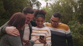 Group of happy diverse friends standing together taking selfie on smartphone in the park