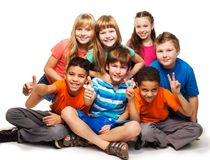 Group of happy diverse looking boys and girs. Group of happy smiling kids sitting together and playing - boys and girls black and Caucasian, isolated on white Stock Photos