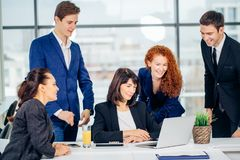 Male and female business people around laptop computer in office. Group of happy diverse male and female business people in formal gathered around laptop Stock Photos