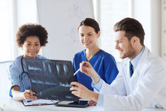 Group of happy doctors discussing x-ray image Stock Image