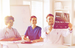 Group of happy doctors discussing x-ray image Stock Images