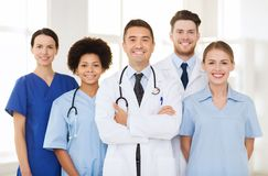 Group of happy doctors at hospital. Hospital, profession, people and medicine concept - group of happy doctors at hospital royalty free stock photo