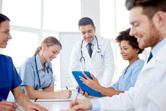 Group of happy doctors meeting at hospital office. Medical education, health care, people and medicine concept - group of happy doctors or interns with mentor Royalty Free Stock Photo