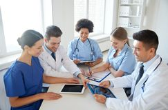 Group of happy doctors meeting at hospital office. Hospital, medical education, health care, people and medicine concept - group of happy doctors with tablet pc Royalty Free Stock Images