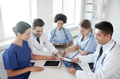 Group of happy doctors meeting at hospital office. Hospital, medical education, health care, people and medicine concept - group of happy doctors with tablet pc Stock Photo