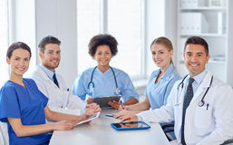 Group of happy doctors meeting at hospital office. Hospital, profession, people and medicine concept - group of happy doctors meeting at medical office royalty free stock photo