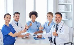 Group of happy doctors meeting at hospital office. Hospital, profession, people and medicine concept - group of happy doctors meeting at medical office royalty free stock photography