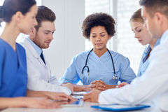 Group of happy doctors meeting at hospital office. Hospital, profession, people and medicine concept - group of happy doctors meeting at medical office royalty free stock image