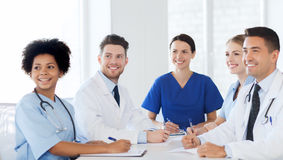 Group of happy doctors meeting at hospital office. Hospital, profession, people and medicine concept - group of happy doctors meeting at medical office royalty free stock photos