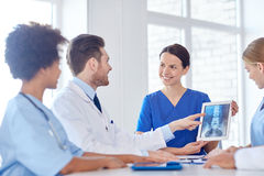 Group of happy doctors meeting at hospital office. Hospital, profession, people and medicine concept - group of happy doctors with tablet pc computers meeting at royalty free stock images