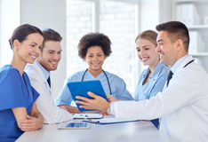 Group of happy doctors meeting at hospital office. Hospital, profession, people and medicine concept - group of happy doctors with tablet pc computers meeting at royalty free stock image