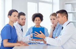 Group of happy doctors meeting at hospital office. Hospital, profession, people and medicine concept - group of happy doctors with tablet pc computers meeting at Stock Image