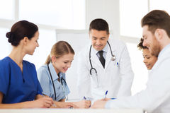 Group of happy doctors meeting at hospital office. Hospital, profession, people and medicine concept - group of happy doctors meeting and taking notes at medical stock images