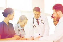 Group of happy doctors meeting at hospital office. Hospital, profession, people and medicine concept - group of happy doctors meeting and taking notes at medical Royalty Free Stock Photography