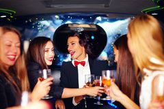Group of happy elegant women clinking glasses in limousine, hen party Royalty Free Stock Photography