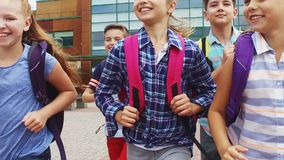 Group of happy elementary school students running. Primary education, communication and people concept - group of happy elementary school students with backpacks stock footage