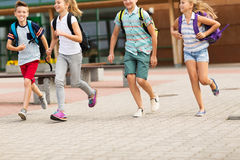 Group of happy elementary school students running. Primary education, friendship, childhood and people concept - group of happy elementary school students with Royalty Free Stock Images