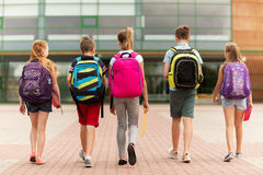 Group of happy elementary school students walking. Primary education, friendship, childhood and people concept - group of happy elementary school students with Stock Image