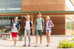 Group of happy elementary school students walking. Primary education, friendship, childhood and people concept - group of happy elementary school students with Royalty Free Stock Image