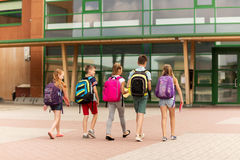 Group of happy elementary school students walking. Primary education, friendship, childhood and people concept - group of happy elementary school students with Royalty Free Stock Photos
