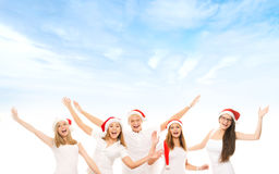 A group of happy and emotional teenagers in Christmas hats posin Royalty Free Stock Photos