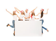 A group of happy and emotional teenagers in Christmas hats posin Royalty Free Stock Photography
