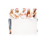 A group of happy and emotional teenagers in Christmas hats Royalty Free Stock Photography