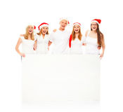 A group of happy and emotional teenagers in Christmas hats Royalty Free Stock Image