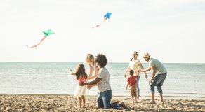 Group of happy families with parent and children playing with kite at beach vacation - Summer joy carefree concept with mixed. Race people having fun together stock image