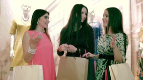 A group of happy female friends having shopping day in huge mall. A group of happy female friends standing together near the shop-window while having shopping stock video footage