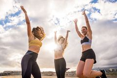 Group of happy females jump at the beach after a fitness session outdoor. attractive ladies enjoy the healthy lifestyle. backlight royalty free stock image