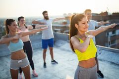 Group of happy fit young people friends in sportswear doing exercises . Sport outdoors stock photo