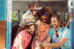 Group of happy friend using mobile phone in campervan Stock Photography