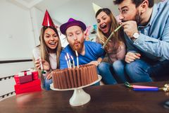 Group of happy friends celebrating birthday at home and having fun. Young group of happy friends celebrating birthday at home and having fun stock images