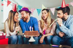 Group of happy friends celebrating birthday at home and having fun. Young group of happy friends celebrating birthday at home and having fun royalty free stock images