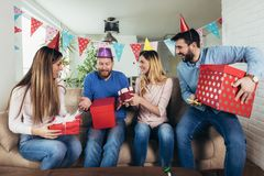 Group of happy friends celebrating birthday at home and having fun. Young group of happy friends celebrating birthday at home and having fun royalty free stock photography
