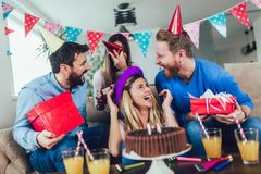 Group of happy friends celebrating birthday at home and having fun stock photography