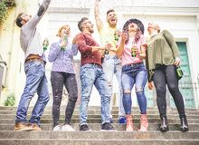 Group of happy friends celebrating together throwing up confetti and drinking beers. Young people having a party on stairs of an urban area in the city stock photos